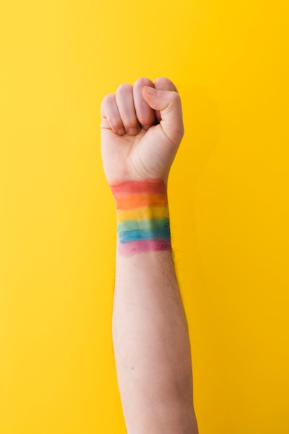 Person holding fist with rainbow flag on wrist Free Photo