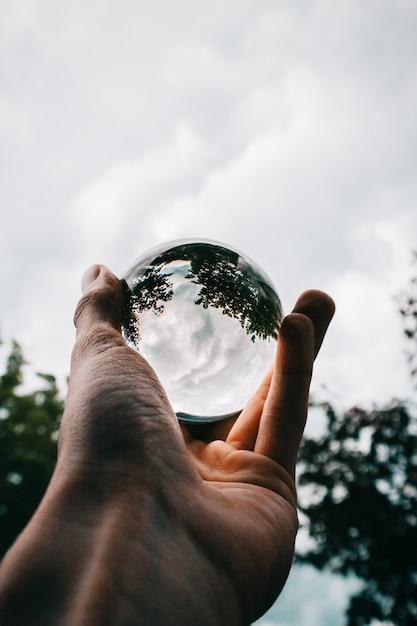 Una persona in possesso di una palla di vetro con il riflesso di bellissimi alberi verdi e nuvole mozzafiato Foto Gratuite