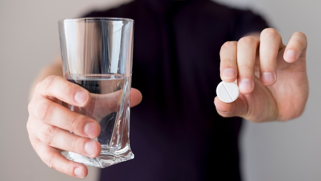 Person holding glass of water and a pill Free Photo