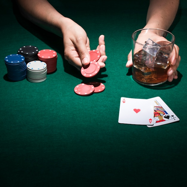 A person holding glass of whiskey while playing poker card Free Photo