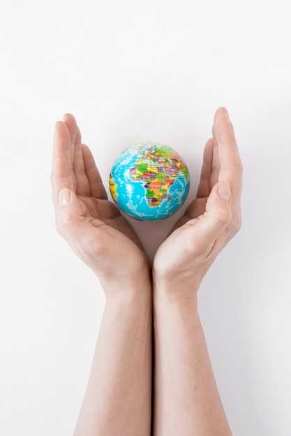 Person holding a globe on white background Free Photo