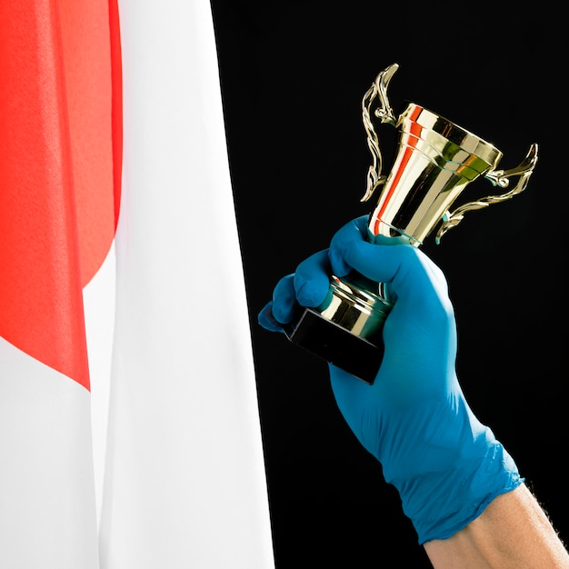 Person holding a golden trophy Free Photo