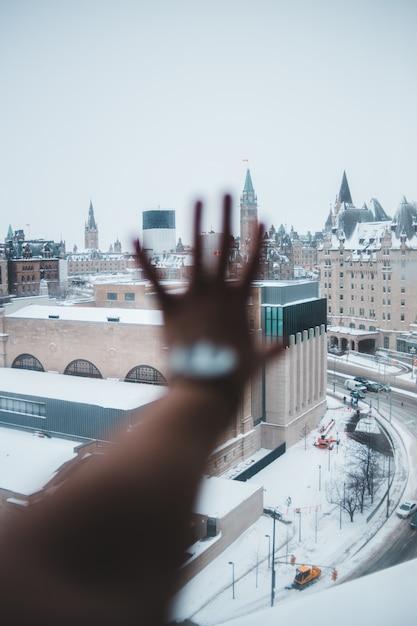 Persona che tiene la mano contro la finestra Foto Gratuite