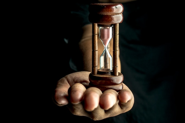 Person holding hourglass against black background Premium Photo