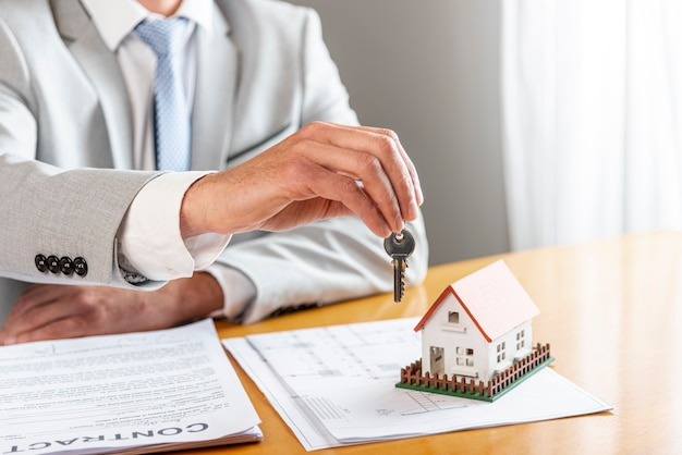 Person holding house keys and toy model house on desk Free Photo