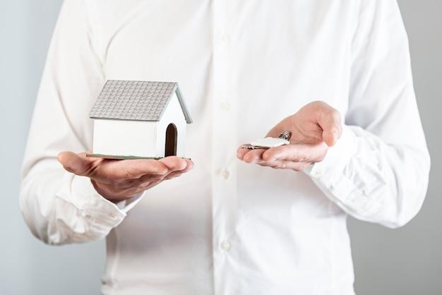 Persona in possesso di un giocattolo di casa e le chiavi Foto Gratuite