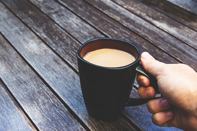 Persona che tiene la sua tazza nera piena di caffè su una superficie di legno Foto Gratuite