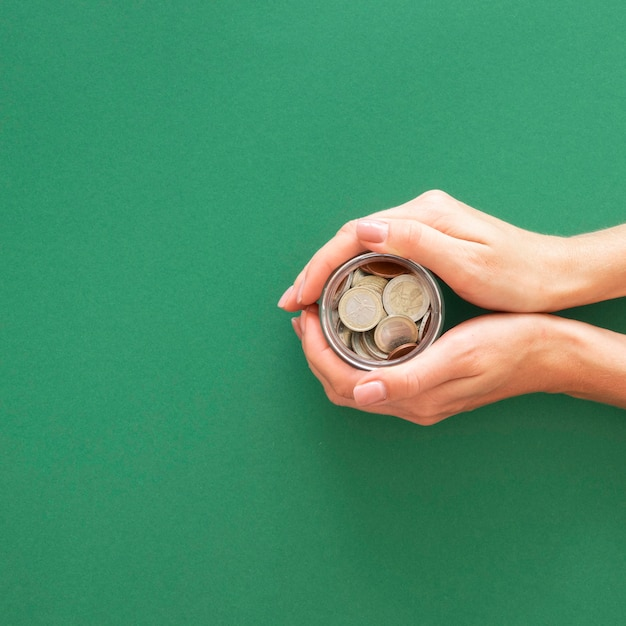 Person holding a jar with coins with copy space Free Photo