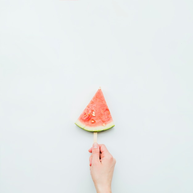 Person holding juicy fresh watermelon popsicle Free Photo