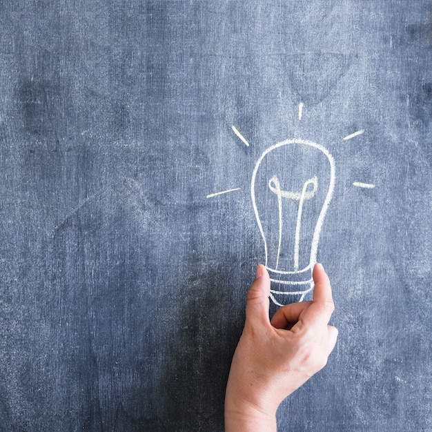 A person holding light bulb drawn on chalkboard Free Photo