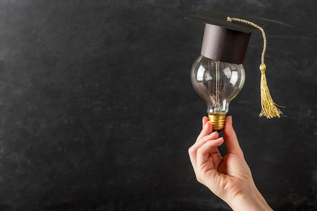 Person holding a light bulb with graduation cap Free Photo