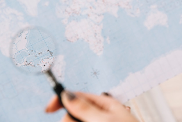 A person holding magnifying glass on map searching for destination Free Photo