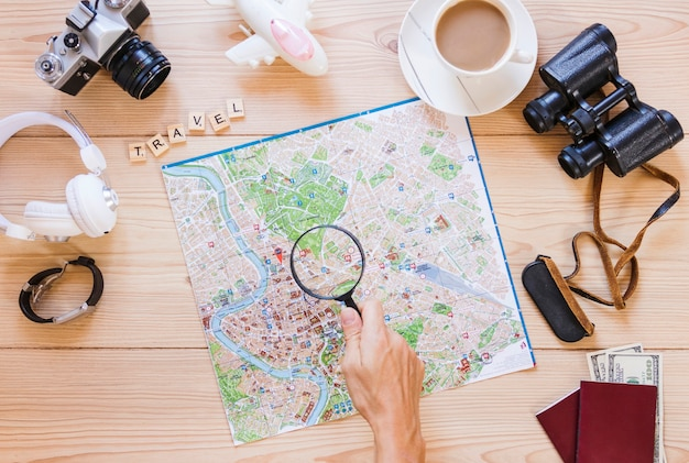 A person holding magnifying glass over map with tea cup and traveling equipment on wooden desk Free Photo