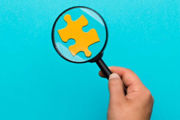 A person holding magnifying glass over the yellow puzzle against blue background Free Photo