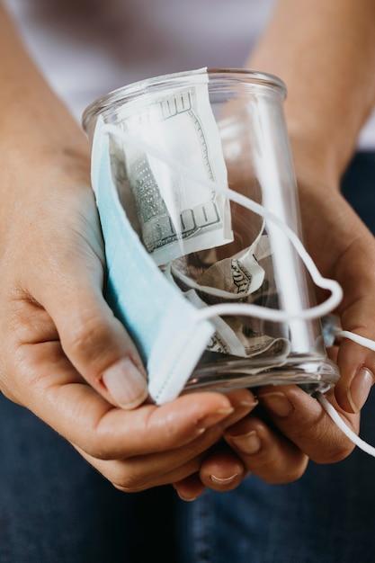 医療用マスクとお金で瓶をクリアを持っている人 Premium写真
