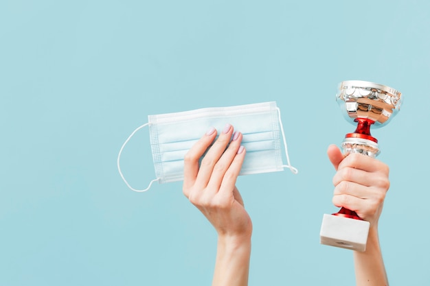 Person holding medical mask and a trophy Premium Photo
