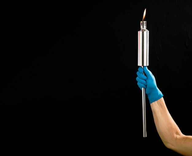 Person holding a metal torch with copy space Free Photo