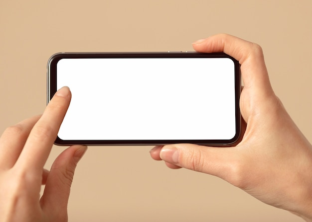 Person holding a mobile phone with white screen Free Photo