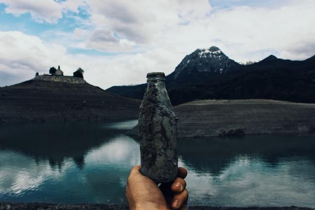 Persona in possesso di una vecchia bottiglia di vetro coperta di fango vicino all'acqua con le montagne Foto Gratuite