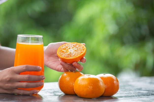 Person holding an orange fruit in her hand Free Photo