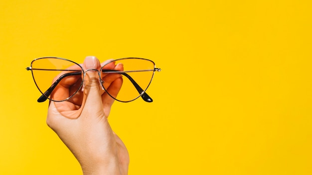 Person holding a pair of modern eyeglasses Free Photo