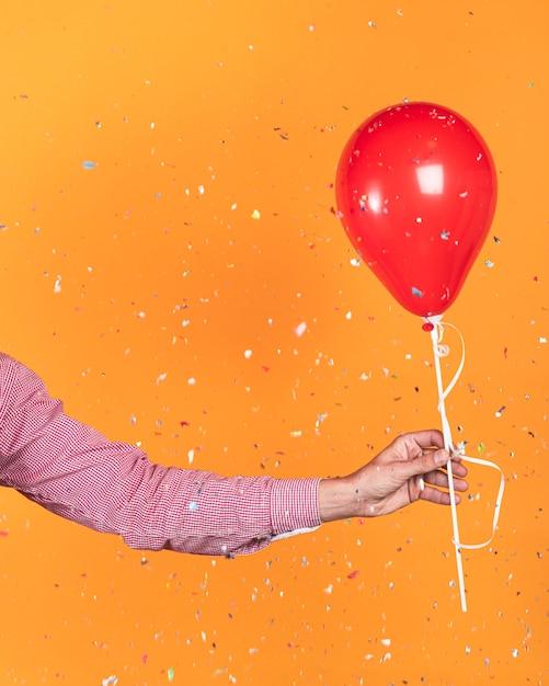 Persona in possesso di un palloncino rosso e coriandoli Foto Gratuite
