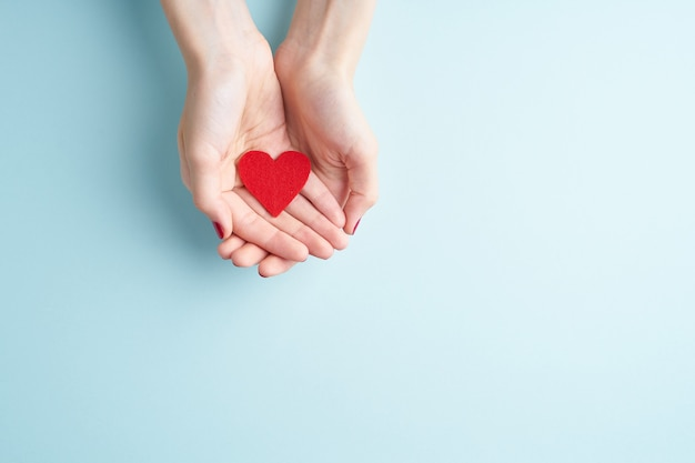 A person holding red heart in hands Premium Photo