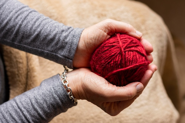 Person holding a red thread for knitting Free Photo