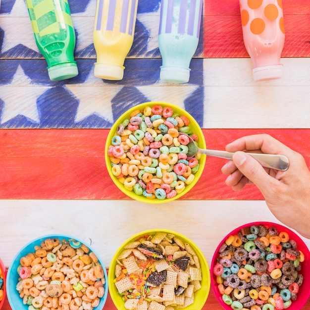 Person holding spoon in bowl of cereal Free Photo
