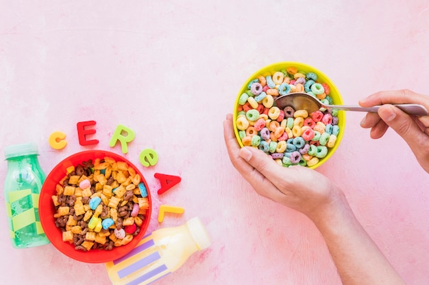 Person holding spoon and bowl near cereal inscription Free Photo