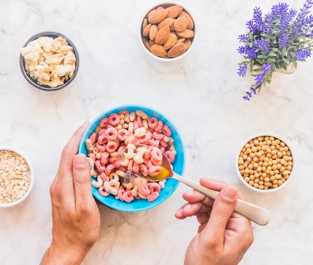 Person holding spoon with cereal above blue bowl Free Photo
