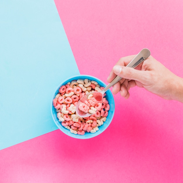 Person holding spoon with cereal above bowl Free Photo