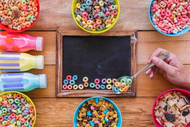 Person holding spoon with cereal above chalkboard Free Photo