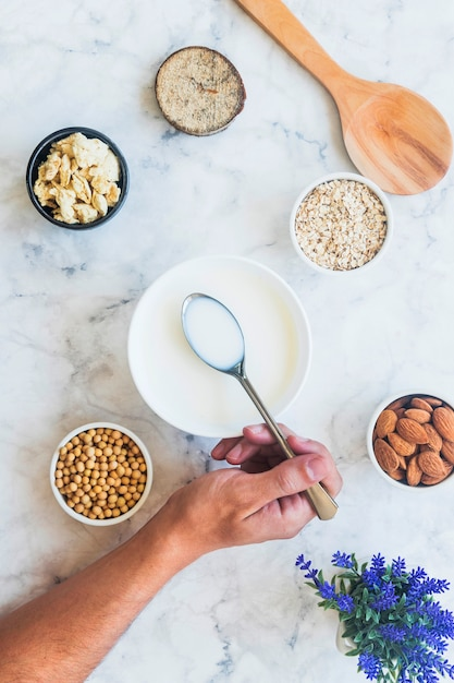 Person holding spoon with milk above bowl on table Free Photo