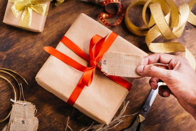 Person holding tag above gift box Free Photo