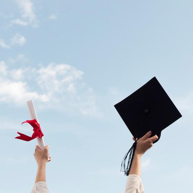卒業式の帽子と卒業証書を持っている人 Premium写真