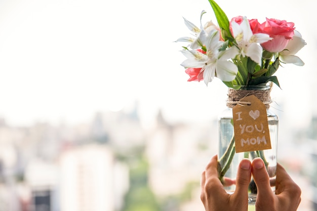 Person holding vase with flowers and i love you mom inscription Free Photo