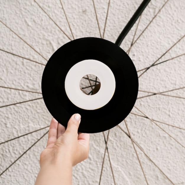 Person holding vinyl record near white wall Free Photo