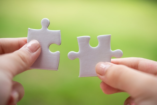 Person holding white puzzle pieces Free Photo
