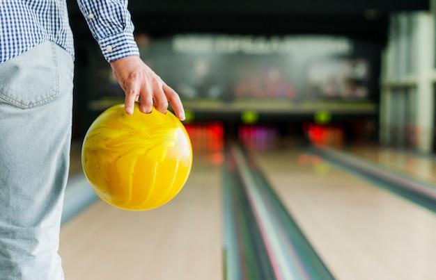 Persona in possesso di una palla da bowling gialla Foto Gratuite