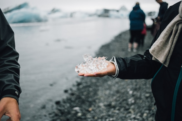 La persona tiene il pezzo di ghiaccio del ghiacciaio in islanda Foto Gratuite
