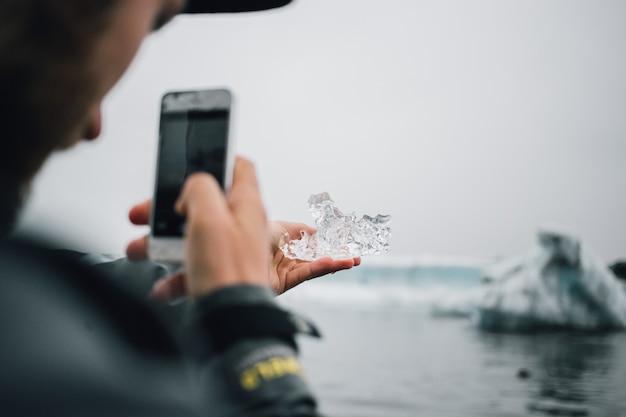 Человек держит кусок ледникового льда в исландии Бесплатные Фотографии