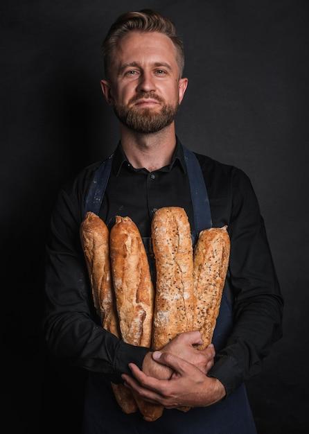 Человек обнимает буханки хлеба, вид спереди Бесплатные Фотографии