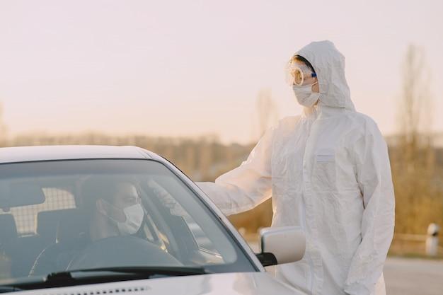 防護服を着た人が温度をチェック 無料写真