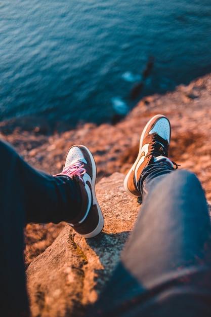 黒いパンツと茶色と白のスニーカーの人が近くの体の近くの茶色の岩の上に座って 無料写真