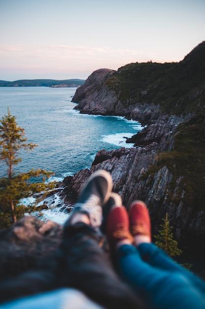 昼間に海の上の崖の上に座っている青いデニムジーンズの人 無料写真