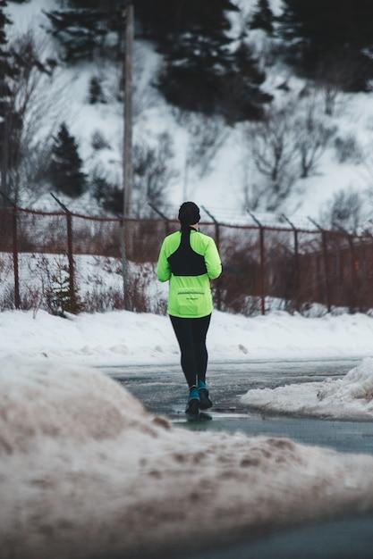 昼間は雪に覆われた地形の近くのコンクリート経路にある緑の長袖トップと黒のヨガパンツの人 無料写真