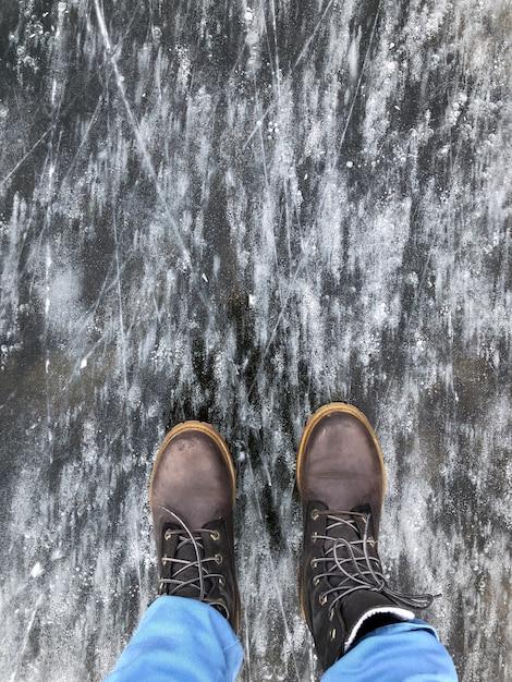 凍ったメタンの泡の湖の表面に立っている重いブーツの人 Premium写真