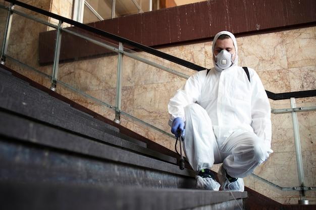 白い化学防護服を着た人が公共の廊下を消毒し、伝染性の高いコロナウイルスの拡散を阻止する手順 無料写真