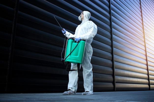 昆虫やげっ歯類を殺すために消毒と害虫駆除を行い、毒を噴霧する白い化学防護服を着た人 無料写真